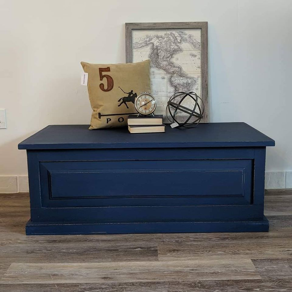 Blanket box painted with navy chalk finish paint pillows books and picture on top