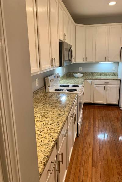 painted kitchen cabinets white with stove microwave and wood floor