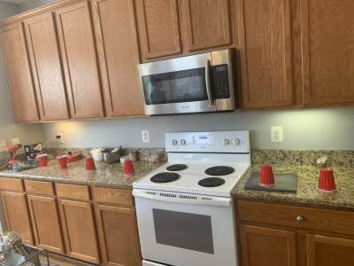 unpainted kitchen cabinets white stove and stainless microwave