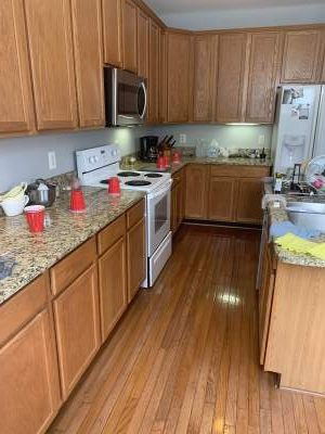 Unpainted kitchen cabinets shot horizontally white stove wood floor and countertop