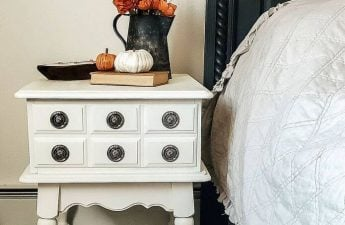 vintage white side table beside bed painted with house and canvas angora