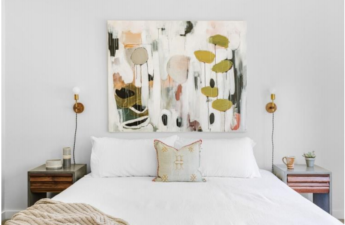 bed with painting and two lamps