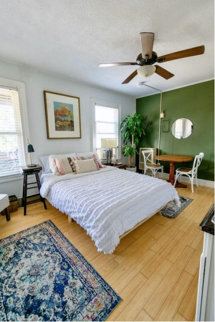 bed in room with green accent wall