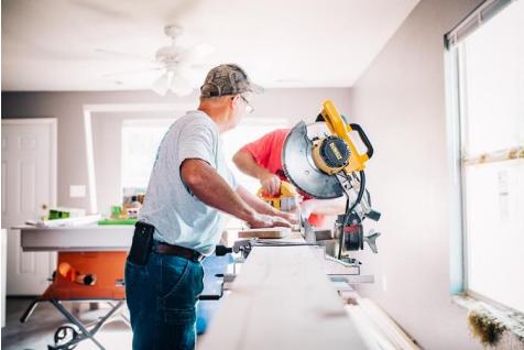 man cutting wood with a chop saw